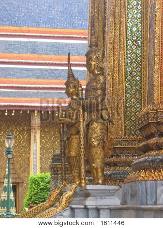 Wat Phra Kaeo And The Grand Palace In Gold With Warrior Statues, Bangkok, Thailand