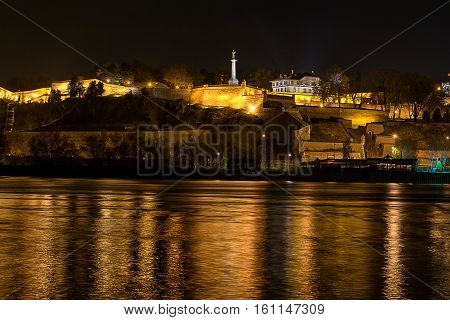Nigh view fo old Belgrade fortress and monument with nice colorful reflection on river surface