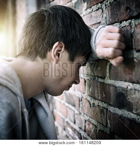 Toned Photo of Sad Young Man by the Old Brick Wall