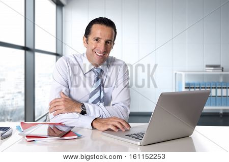 40 to 50 years old senior businessman working on computer laptop sitting at desk looking confident relaxed and successful smiling happy at modern business district office in success concept