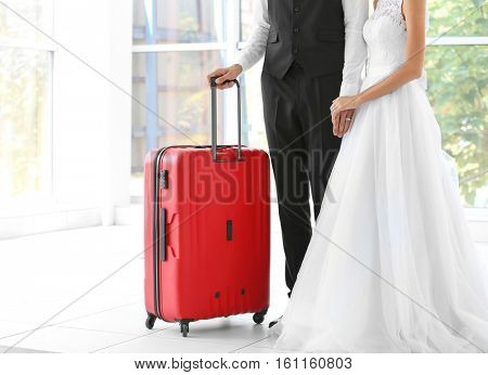 Groom and bride with big suitcase indoors