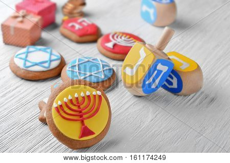 Tasty glazed cookies and dreidels for Hanukkah on light wooden table, closeup