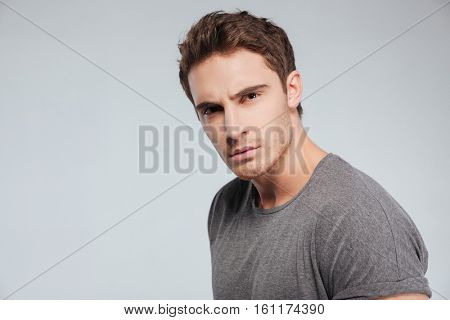Close up portrait of a serious casual man staring at camera over white background