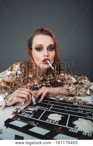 Beautiful addicted young woman actress smoking and taking drugs
