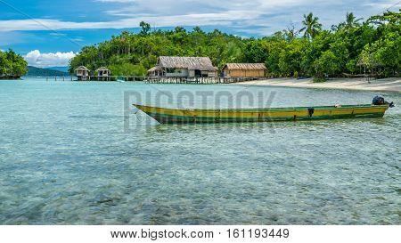 Papua Local Boat, Beautiful Blue Lagoone near Kordiris Homestay, Small Green Island and Homespay in Background, Gam Island, West Papuan, Raja Ampat, Indonesia
