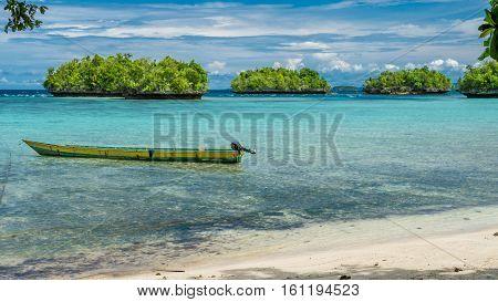 Papua Local Boat, Beautiful Blue Lagoone near Kordiris Homestay, Small Green Island in Background, Gam Island, West Papuan, Raja Ampat. Indonesia