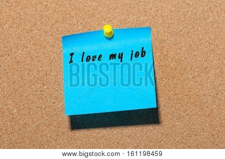 I love my job - words on blue sticker pinned at cork notice board.