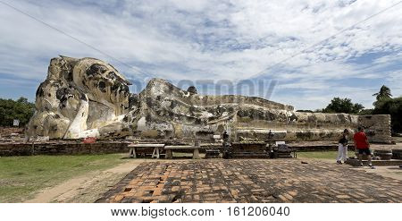 AYUTTHAYA, THAILAND - November 4, 2016: View of the small altar where devotees bring offerings to the reclining Buddha behind at Wat Lokaya Sutha monastery in Ayutthaya Thailand