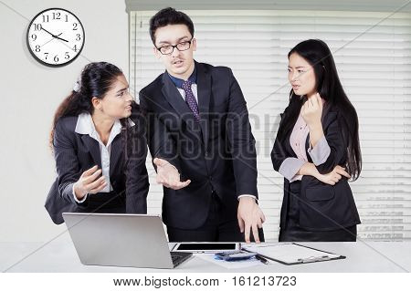 Three young businesspeople standing in the office while discussing and debating with a laptop on desk