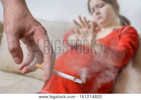 Passive Smoking In Pregnancy. Selfish Man Is Smoking Cigarette.