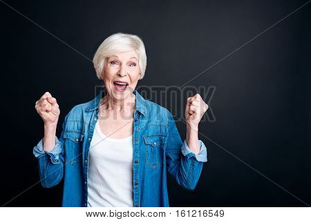 True emotions. Positive aged woman feeling jubilated and smiling while looking at you