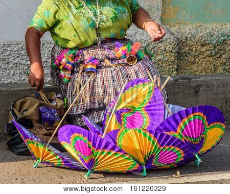Cuidad Vieja, Guatemala - December 7 2016: Indigenous Mayan woman wearing traditional handwoven blouse (huipil) selling handmade paper parasols at Virgin of the Immaculate Conception street parade