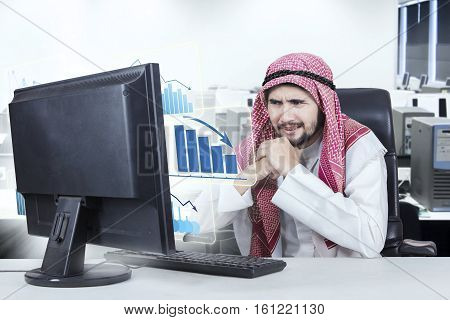 Image of confused male entrepreneur looking at a virtual decline graph on the monitor