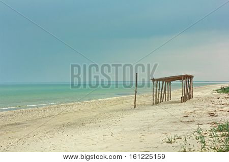 Wild beach. Seascape. Coast. On the beach the sand was an old wooden bungalow. The roof is covered tsuhim rostnikom. The sea of azure blue. The sky is clear, sunny day. Water is clear. Picture a tourist directory. The sand is growing reed or cane. Water a