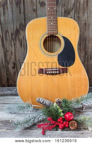 acoustic guitar with christmas decor on a wood background