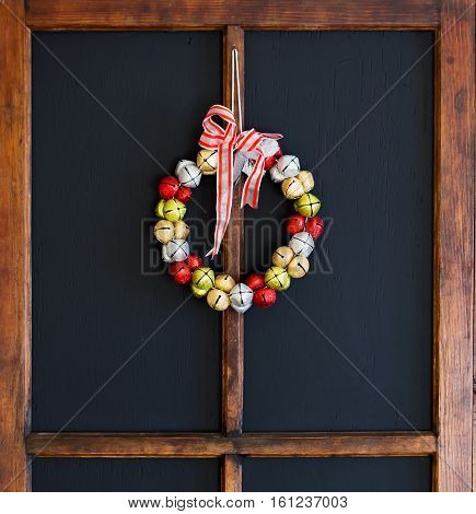 A red silver gold and green jingle bell Christmas wreath on a black background