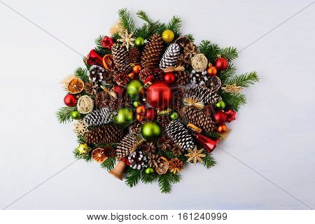 Christmas wreath with fir branches pine cones and rustic ornaments. Christmas decoration with baubles jingle bells and dried orange slices.
