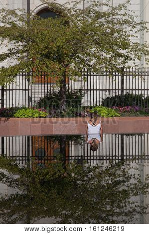 Girl sits under tree by pond with reflection in foreground
