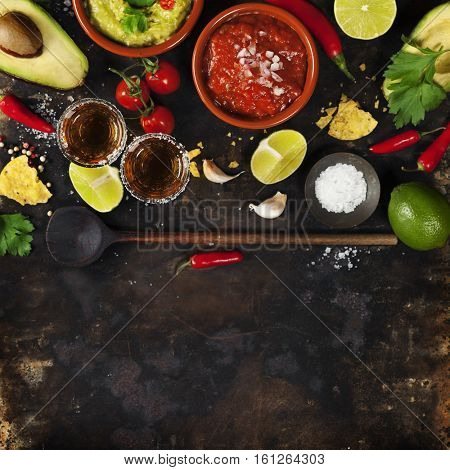 Mixed mexican food background. Party food. Guacamole,nachos, salsa, peppers, tomatoes, avocado and tequila shots on a rustic table.Tex-mex cuisine. Assorted appetizers. Food frame