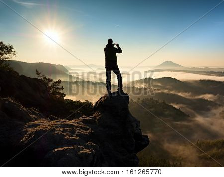 Tourist Takes Photos With Smart Phone On Peak Of Hilly Landscape. Autumn Fogy Hills