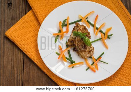 Fish coated in crumbs. Wooden rustic background