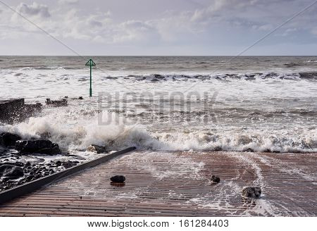 Late winter waves breaking near the jetty and a groyne marker beacon at Tywyn Gwynedd Wales