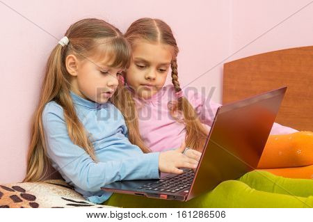 Two Girls Pushing A Search Query On A Laptop Keyboard