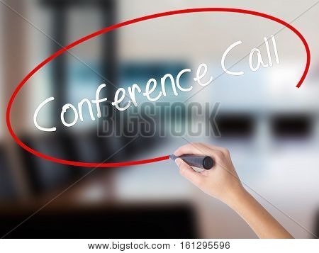 Woman Hand Writing Conference Call With A Marker Over Transparent Board.
