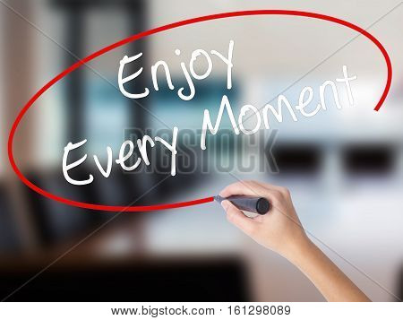 Woman Hand Writing Enjoy Every Moment With A Marker Over Transparent Board.