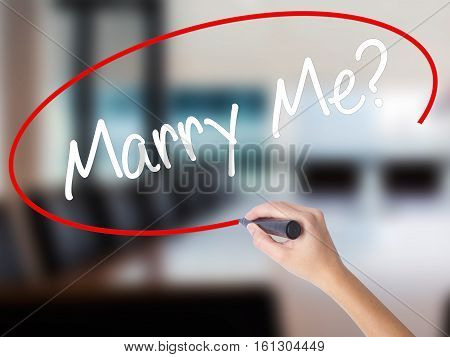 Woman Hand Writing Marry Me? With A Marker Over Transparent Board.