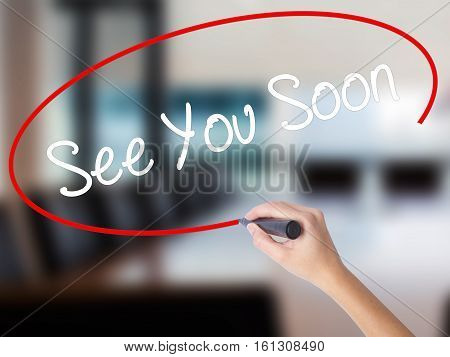 Woman Hand Writing See You Soon With A Marker Over Transparent Board.