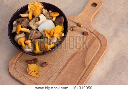 Raw Food. Bowl With Raw Cut Edible Mushrooms (chanterelles Ceps) And Cutting Wooden Board On Beige Brown Background Top View.