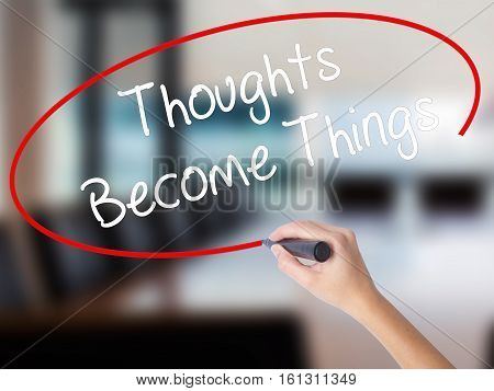 Woman Hand Writing Thoughts Become Things With A Marker Over Transparent Board