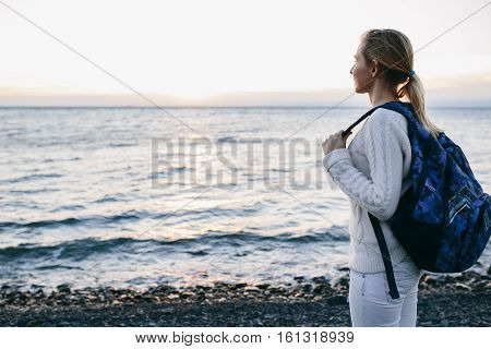 Young woman tourist in a white clothing standing on the shore and looks at sea