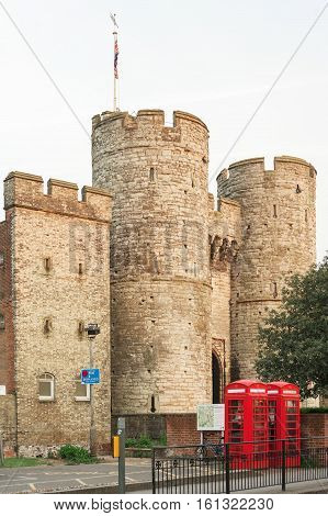 The Westgate is a 14th century medieval gatehouse in Canterbury Kent England. This western gate of the city wall is the largest surviving city gate in England. Twins british red phone booth K6 against a Roman wall into the summer sunset.