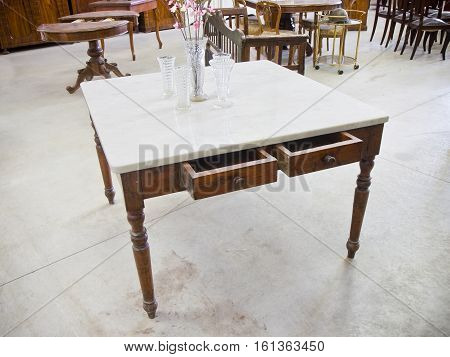 Old italian table just restored in a junk shop with top in white Carrara marble