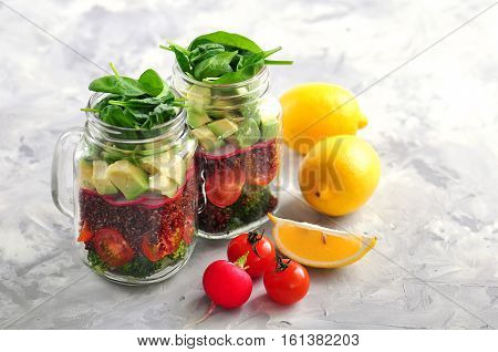 Healthy salad with quinoa, avocado, tomato, red onion, baby spinach, radish and olive oil in a Mason jars.