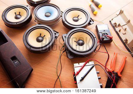 Tweaking audio. Car audio speakers on a work table.