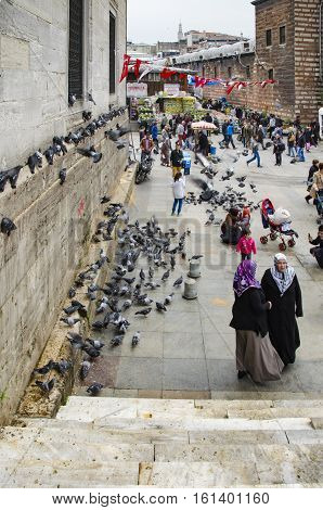 Istanbul Turkey - March 29 2013: New Mosque (Yeni Cami) People and pigeons around the courtyard. It is situated on the Golden Horn at the southern end of the Galata Bridge and is one of the famous architectural landmarks of Istanbul.