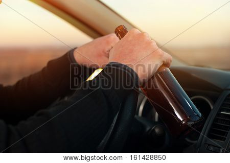Male hands on steering wheel with beer bottle. Driving under alcohol influence.