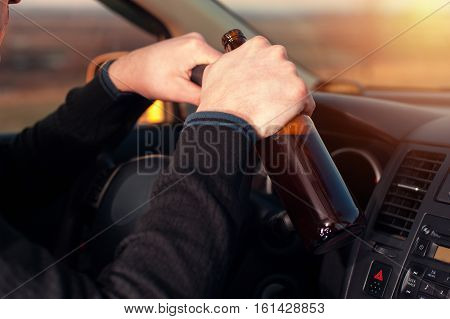 Cropped shot of young drunk man driving a car and drinking beer. Dangerous driving.