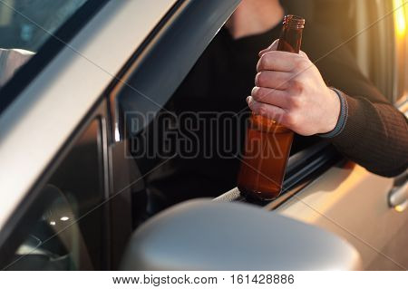 Driving car under alcohol influence. Young man drinking beer in car. Don't drink and drive.