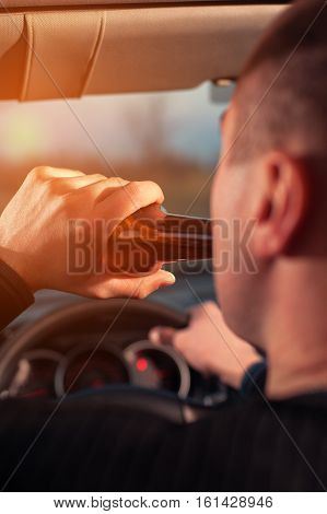 Young man drinking beer while driving a car. Don't drink and drive.
