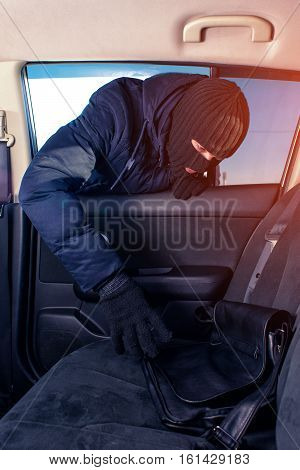 Robber in black mask unlocking the window and stealing forgotten bag from car