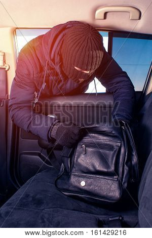 Thief In Robbery Mask Stealing Handbag From Car