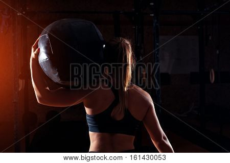 Strong blonde girl holding heavy ball on shoulders.