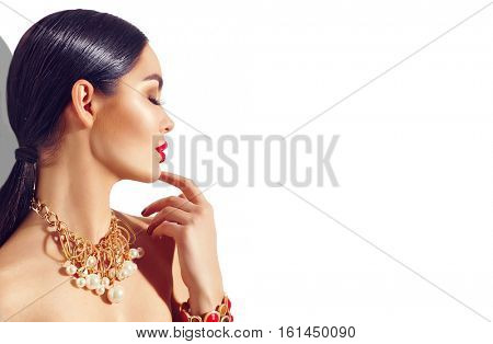 Beauty fashion brunette model girl portrait. Sexy young woman with perfect makeup and trendy golden accessories. Red lips, smooth skin and black hair. High fashion glamour female profile isolated
