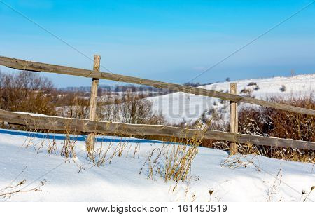 wooden fence on winder meadow in sunny day