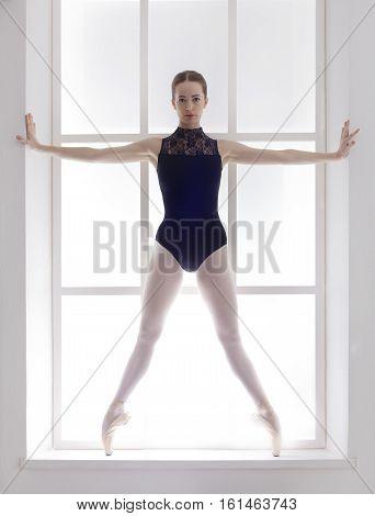 Classical Ballet dancer portrait. Beautiful graceful ballerine in black practice releve ballet position near large window in light hall. Ballet class training, high-key soft toning. Vertical image