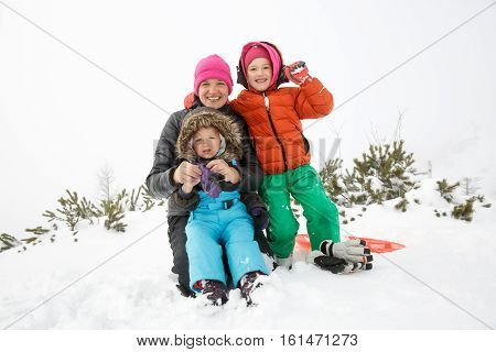 Mother with daughter and son together in a snowy winter landscape bonding having fun smiling and enjoying family time. Mothers day family values parents love and happy childhood concept.